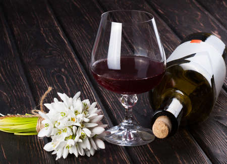 Black bottle of wine and wineglass and snowdrop on the wood background