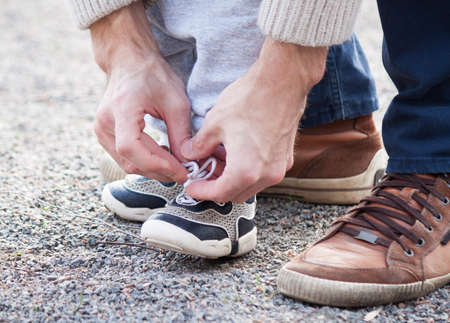 Dad tying the laces on a child sneakers 免版税图像