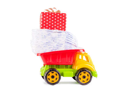incontinence: toy truck with a pile of diapers on the back isolated on white background