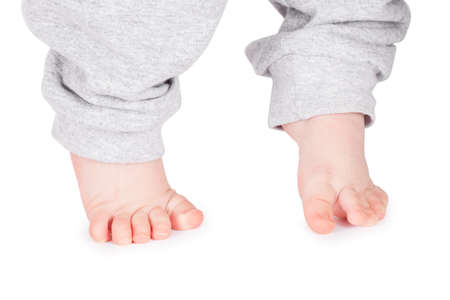 Baby legs on a white background. Children's feet in the pants Standard-Bild