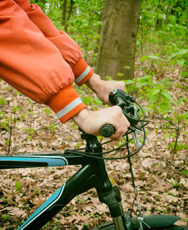 handlebar: Retro photo. Hands in holding handlebar of a bicycle in forest