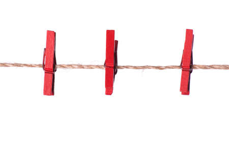 clench: Red clothespins on a rope on a white background