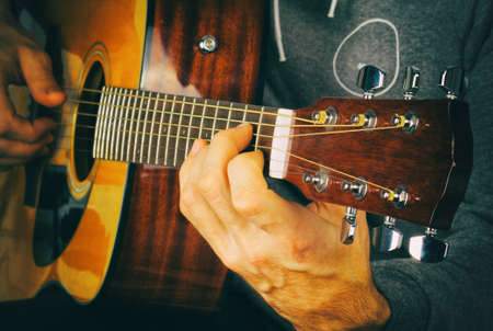 chord: Retro photo with noise texture. Mans hand playing the guitar. Setting a chord on the guitar