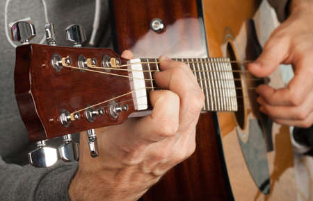 chord: Mans hand playing the guitar. Setting a chord on the guitar Stock Photo
