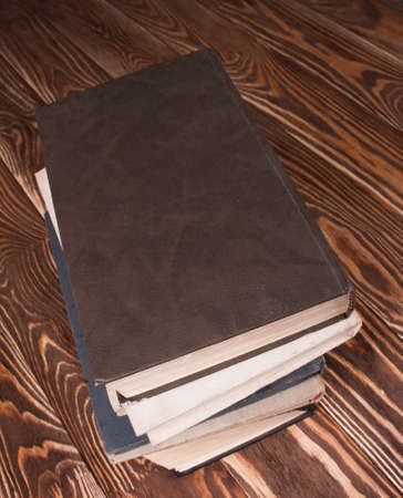 untidiness: Old books on wood desk. Stock Photo