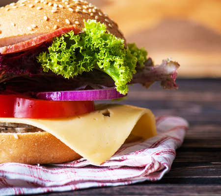 Burger full face with vegetables on wood desk. Meat hamburger. Stock Photo