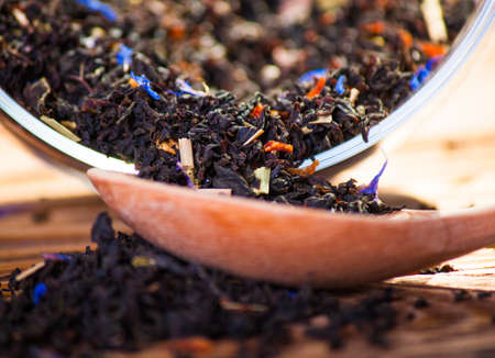 unpressed: Black leaf tea with additives and a wooden spoon on the board Stock Photo