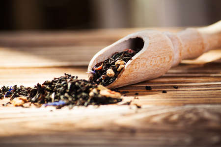 Black leaf tea with additives and a wooden spoon on the board Stock Photo