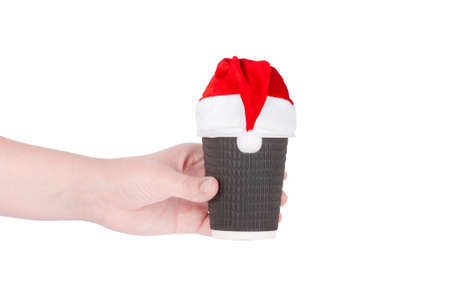 christmas hats: disposable cup of coffee in santa hat  in hand isolated on white background