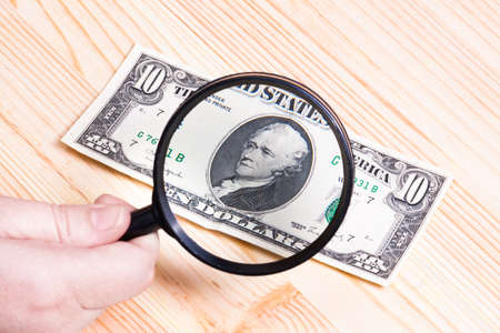Dollar bills and magnifier. Stock Photo