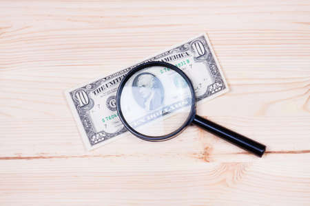 counterfeiting: Dollar bills and magnifier. Stock Photo