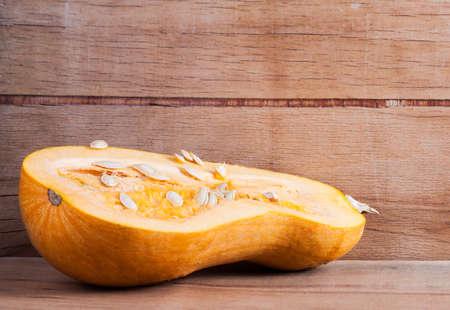 Ripe cut pumpkin on wood desk. Stock Photo