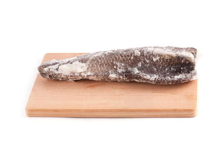 whitefish: Frozen sea fish on a wooden chopping board isolated on white background