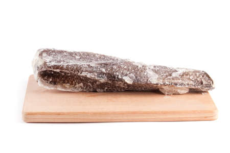 Frozen sea fish on a wooden chopping board isolated on white background