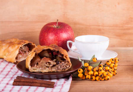 strudel: Piece of apple strudel and coffee cup on wood desk. Stock Photo