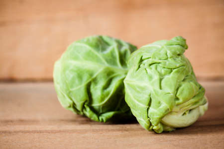 Ripe fresh brussels sprouts on wood board. Stock Photo