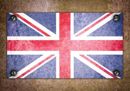 screwed: British flag on a metal plate screwed screws. Old grunge background