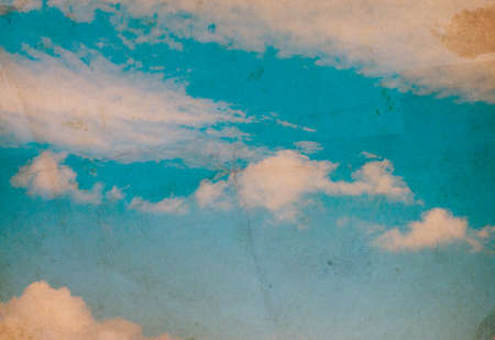 Retro photo with noisy texture. Blue sky with clouds.