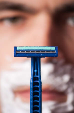 metrosexual: Time for new razor. Close-up young shirtless man holding razor