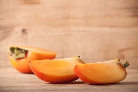 Ripe fresh persimmon on wood board. Food ingredient. Fruits. Stock Photo