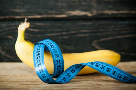 Fresh banana and measuring tape on wood desk Standard-Bild