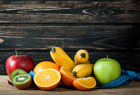 Fresh fruits and measuring tape on wood desk