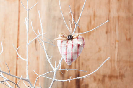 Heart from cloth on white branch. Valentines day background