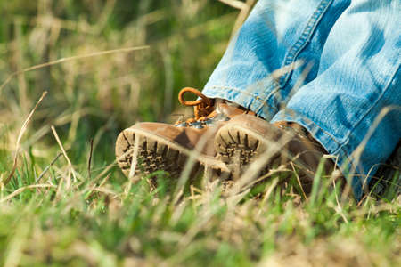 leatherette: Closeup of childrens legs and feet in brown leather boots in nature.