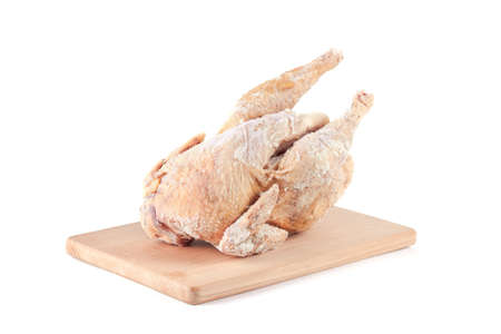 Frozen chicken carcass on a wooden chopping board isolated on white background Stock Photo