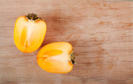 Fresh ripe persimmon close up on wood desk. Nature background