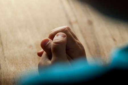reverent: Child hands folded for prayer on wood table