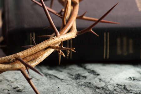 Kroon van doornen en Bijbel op houten bureau. Houtkruis. Concept liefde