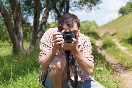 Man photographer with camera in nature. Proffesion concept