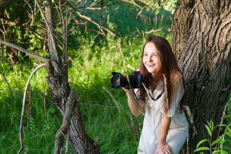 Young woman outdoors portrait with camera. Soft sunny colors.