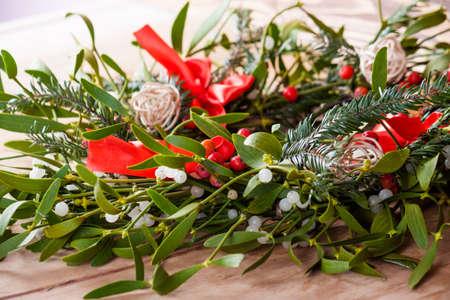 Christmas wreath with mistletoe on wood board. Christmas decoration.