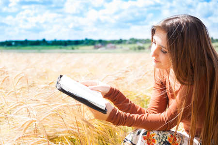free education: Fashion beautiful girl in the field with yellow spikelets on the sky background with book