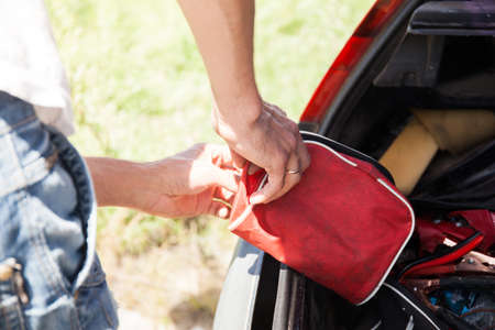 The man is lying first-aid kit in the trunk of the car Stock Photo