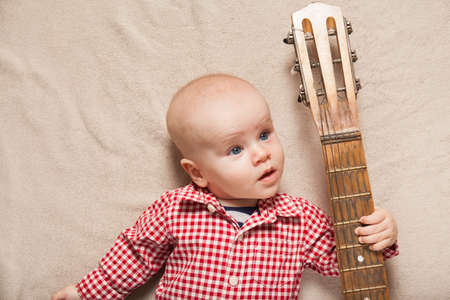 Small child boy with guitar on bed