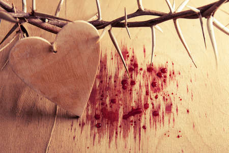 Crown of thorns with blood on wood desk