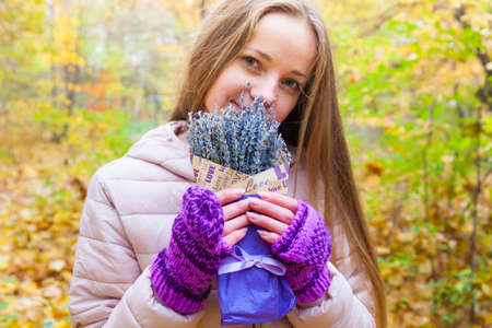 Beautiful young  girl in violet mittens with heart