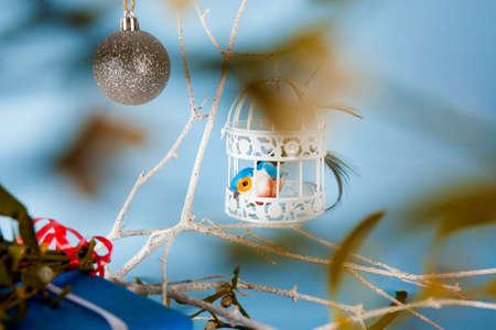 White bird cage and bird on blue background
