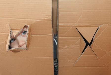 The child peeps through the hole in the paper box Stock Photo