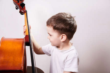 Little boy with cello. learns to play a musical instrument