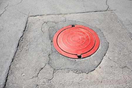 red sewer on asphalt outdoor. city infrastructure Stock Photo