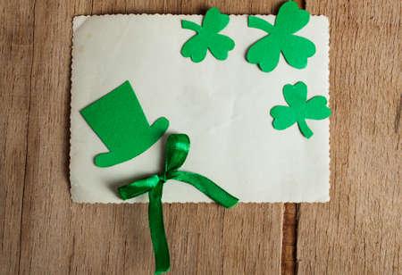 St Patricks Day side border of paper shamrocks over a green wood background