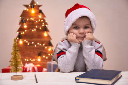 Kid in Santa Hat Writing Wish List, unfocused lights background