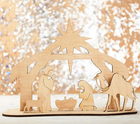 Christmas Nativity Scene of baby Jesus in the manger with Mary and Joseph in silhouette surrounded by the animals and wise men with the city of Bethlehem in the distance with