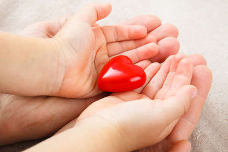 adult and child hands holding red heart, health care, donate and family insurance concept,world heart day, world health day, CSR concept Stok Fotoğraf