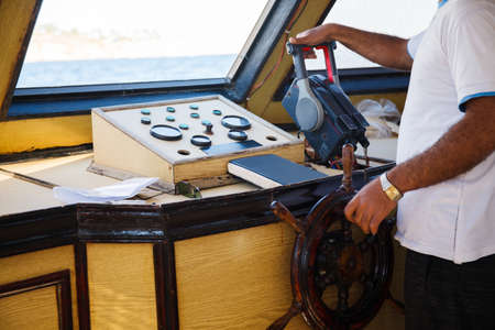 close up of senior man steering wheel and navigating sail boat or yacht floating in sea. travel and people concept
