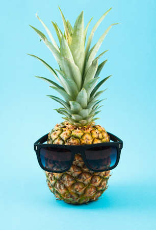 Fresh ripe pineapple on blue background. Food ingredients